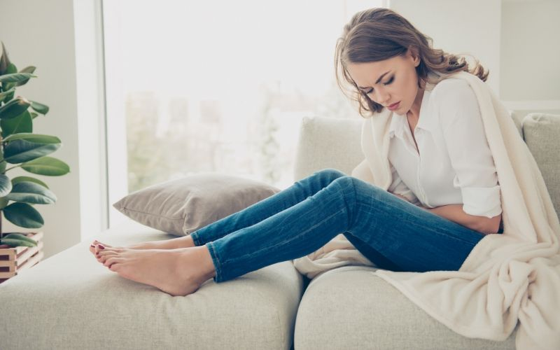 Frau sitzt auf dem Sofa, mit gekrümmter Haltung und Bauchschmerzen.