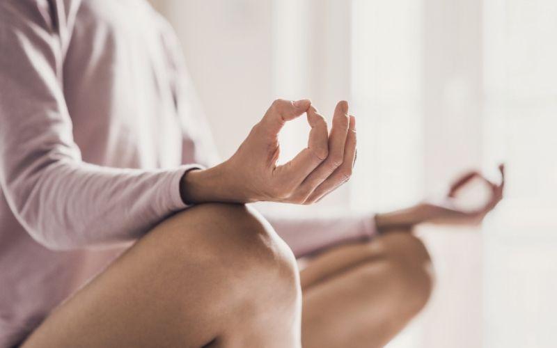 Frau mit rosafarbenem Oberteil sitzt im Schneidersitz, einer Meditationspose und hält ihre Hände zu einem Mudra – Daumen und Zeigefinger berühren sich jeweils –auf ihren Knien.