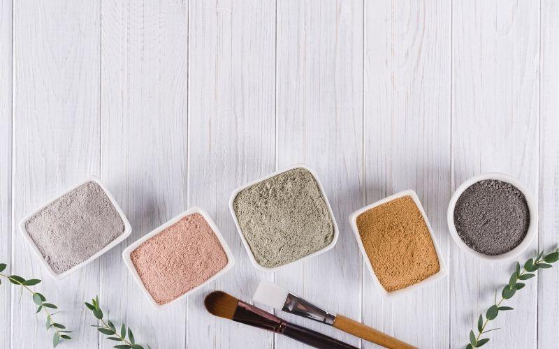 Fünf kleine viereckige Schälchen, in denen jeweils Pulver in einer unterschiedlichen Farbe ist. Davor liegen Pinsel zum Auftragen der Heilerde auf das Gesicht.