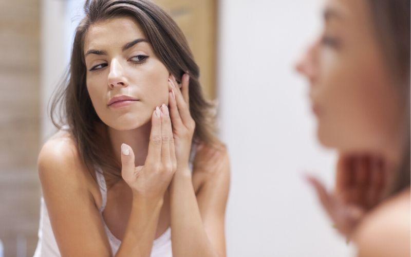 Dunkelhaarige Frau steht vor einem Spiegel und betrachtet die Haut in ihrem Gesicht.