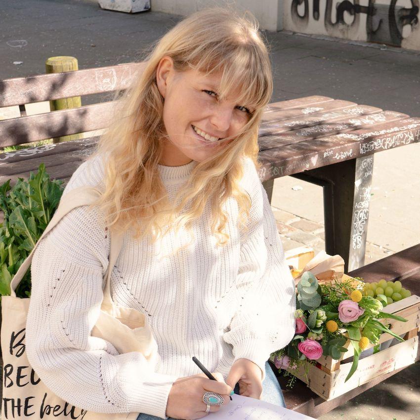 Julia Lang –Blonde Frau sitzt auf einer Bank und hält Notizbuch und Stift in der Hand. Lächelt in die Kamera.