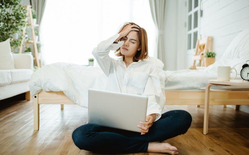 Frau sitzt im Schneidersitz auf dem Boden und hat einen Laptop auf dem Schoß. Sie hält sich den Kopf.