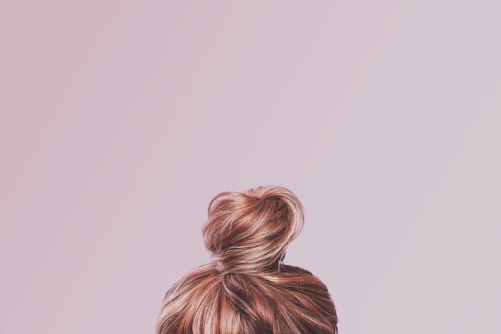 zusammengebundene-haare-vor-hellrosa-wand-kein-gesicht-nur-haarschopf