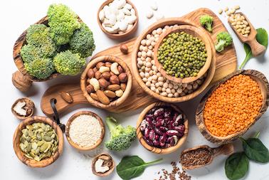 unterschiedliche-protein-und-vitamin-quellen-nüsse-linsen-brokkoli-in-schaelchen-auf-einem-holzbrett