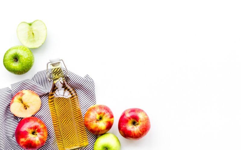 Glasflasche mit gelblicher Flüssigkeit (Apfelessig) liegt auf einem gestreiften Küchenhandtuch. Daneben sind Äpfel in unterschiedlichen Farben zu sehen. Der Hintergrund ist weiß.
