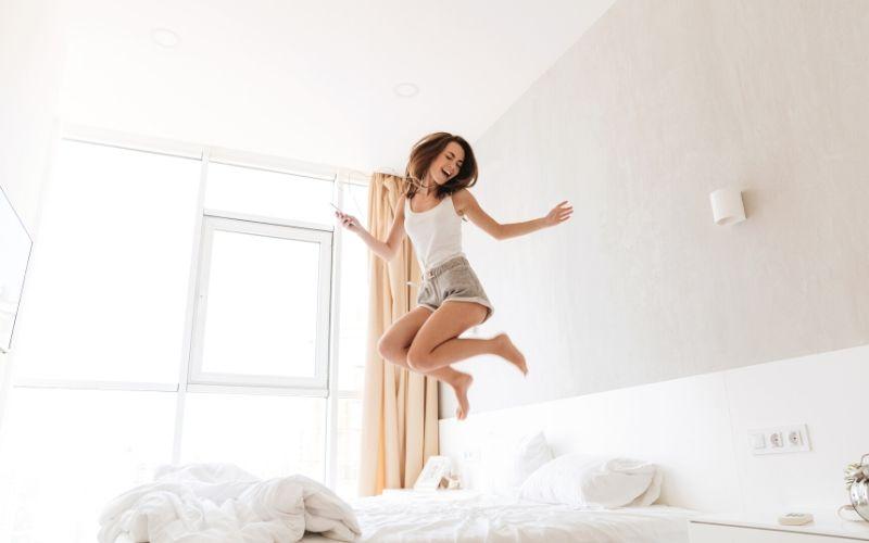 Fröhlich aussehende Frau springt auf dem Bett mit weißen Bettlaken.