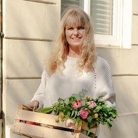 Blonde Frau hält Obstkiste gefüllt mit frischem Gemüse und Obst in der Hand. Sie steht draußen vor einer Hauswand.