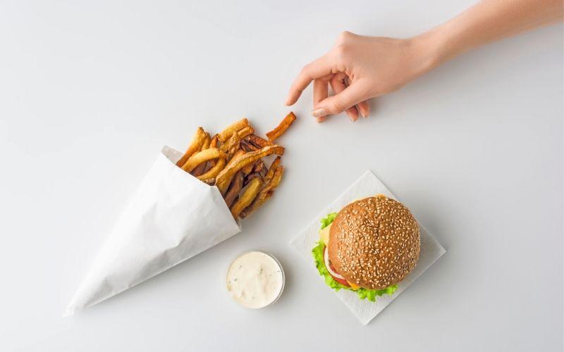 Eine Tüte Pommes und ein Burger mit Majo auf einem weißen Tisch