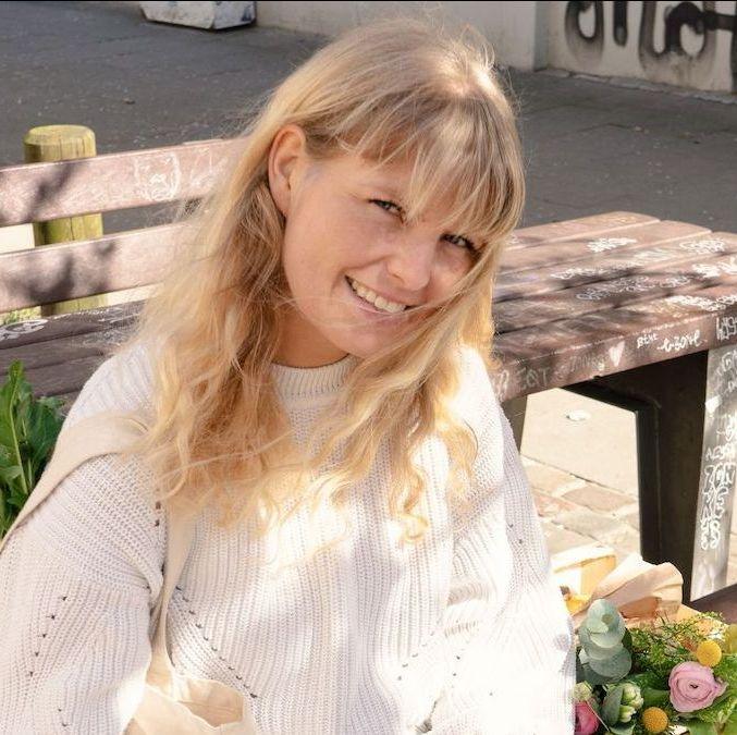 Julia von InnoNature, eine blonde Frau mit hellem Strickpullover, sitzt auf einer Bank im Freien und lächelt in die Kamera.