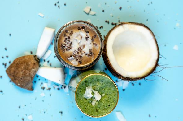 zwei-glaeser-eins-mit-braunem-shake-eins-mit-gruenem-shake-daneben-kokosnusshälften-und-kakaonibs-auf-blauem-untergrund