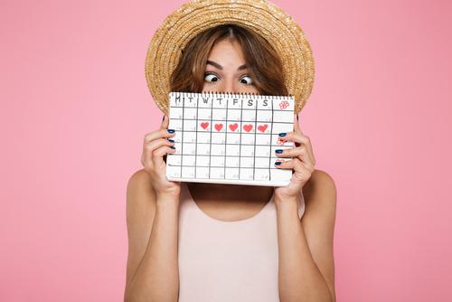 Frau mit Strohhut hält sich Zykluskalender vor das Gesicht