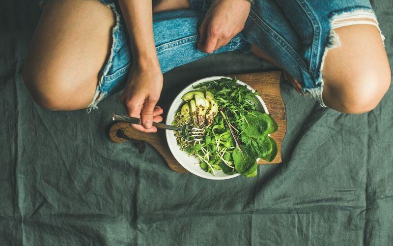 Frau im Schneidersitz hat vor sich eine Schüssel mit grünem Salat, Avocado und Rucola. Sie hält eine Gabel in die Schale.