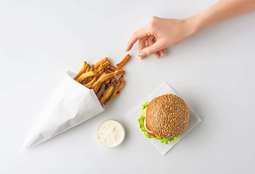 Hand mit greift eine einzelne Pommes aus einer kleinen weißen Papiertüte in der weitere Pommes liegen.