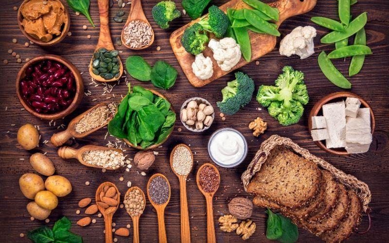 Lebensmittel wie Samen und Haferflocken mit einem hohen Zinkanteil auf einem Holztisch