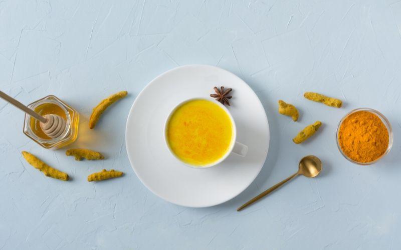 Tasse mit Goldener Milch auf Untertasse daneben Loeffel und Kurkuma Knollen