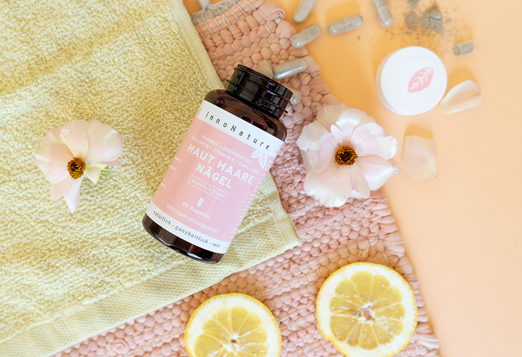 Ein schwarzer Drahtkorb steht auf einem rosa Teppich. Daneben sind Zitronenscheiben und Kosmetikartikel zu sehen. In dem Korb sind InnoNature Nahrungsergänzungsmittel sowie ein Glas mit Pinseln und Handtücher zu sehen.