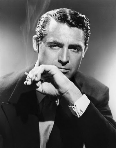 Actor Cary Grant wearing a suit and smoking a cigarette with slicked-back hair.