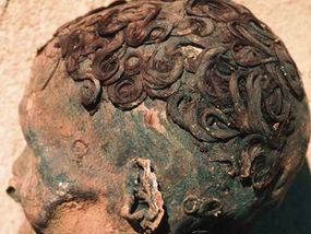 Old carving of a man with curly hair slicked to his head with gel.