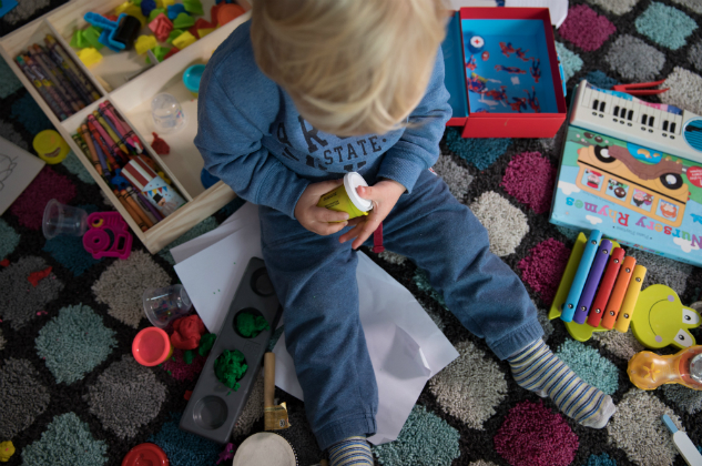 A little boy sits surrounded by toys