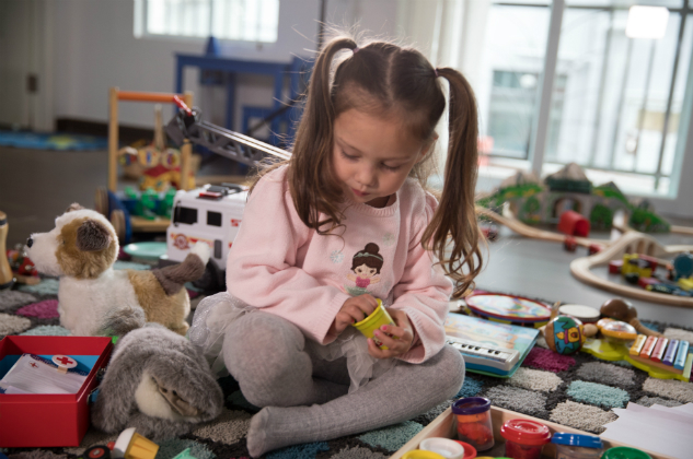 Little girls sits in a playroom surrounded by toys