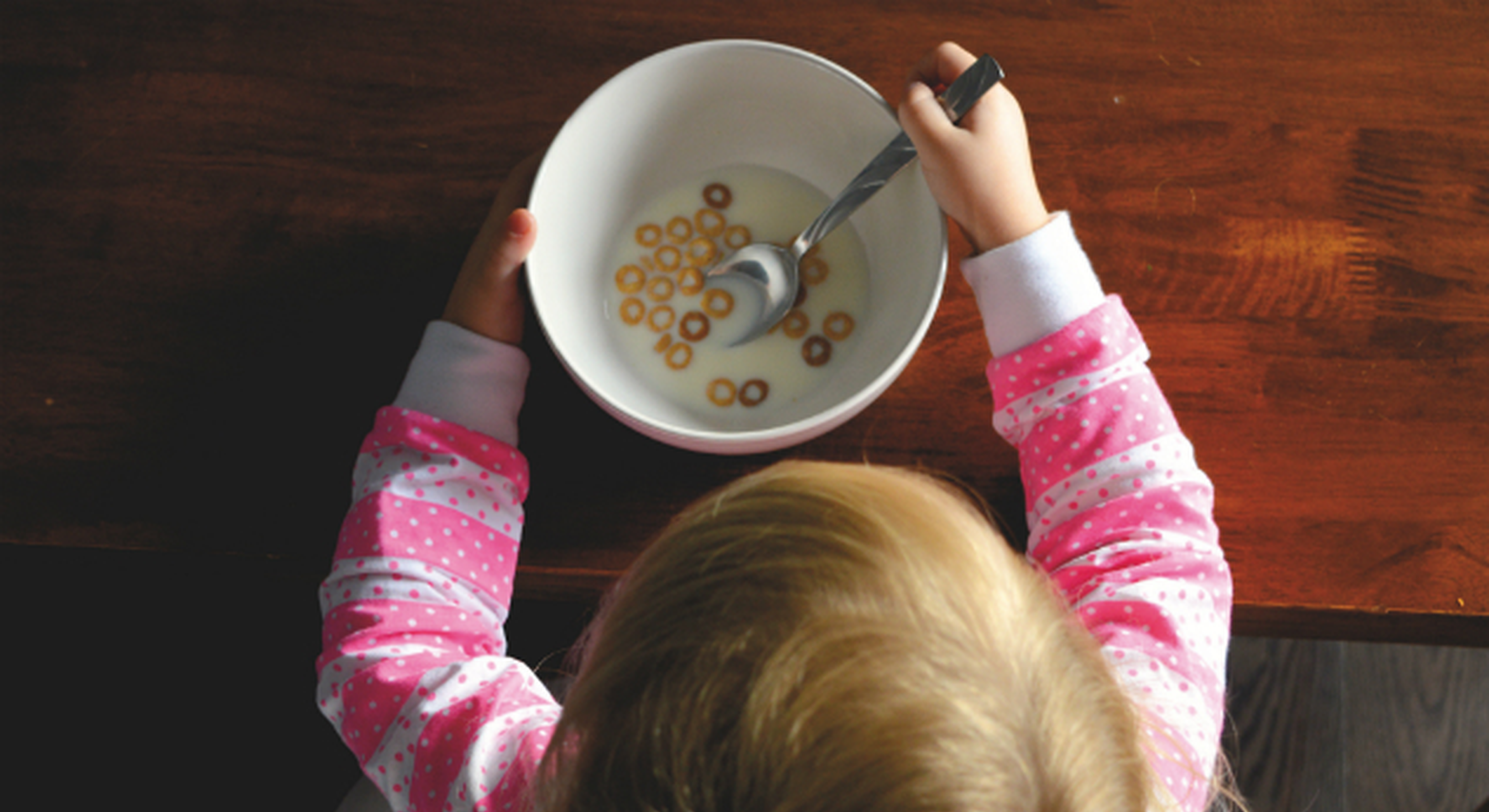 Little girl eating bowl of Cheerios and milk