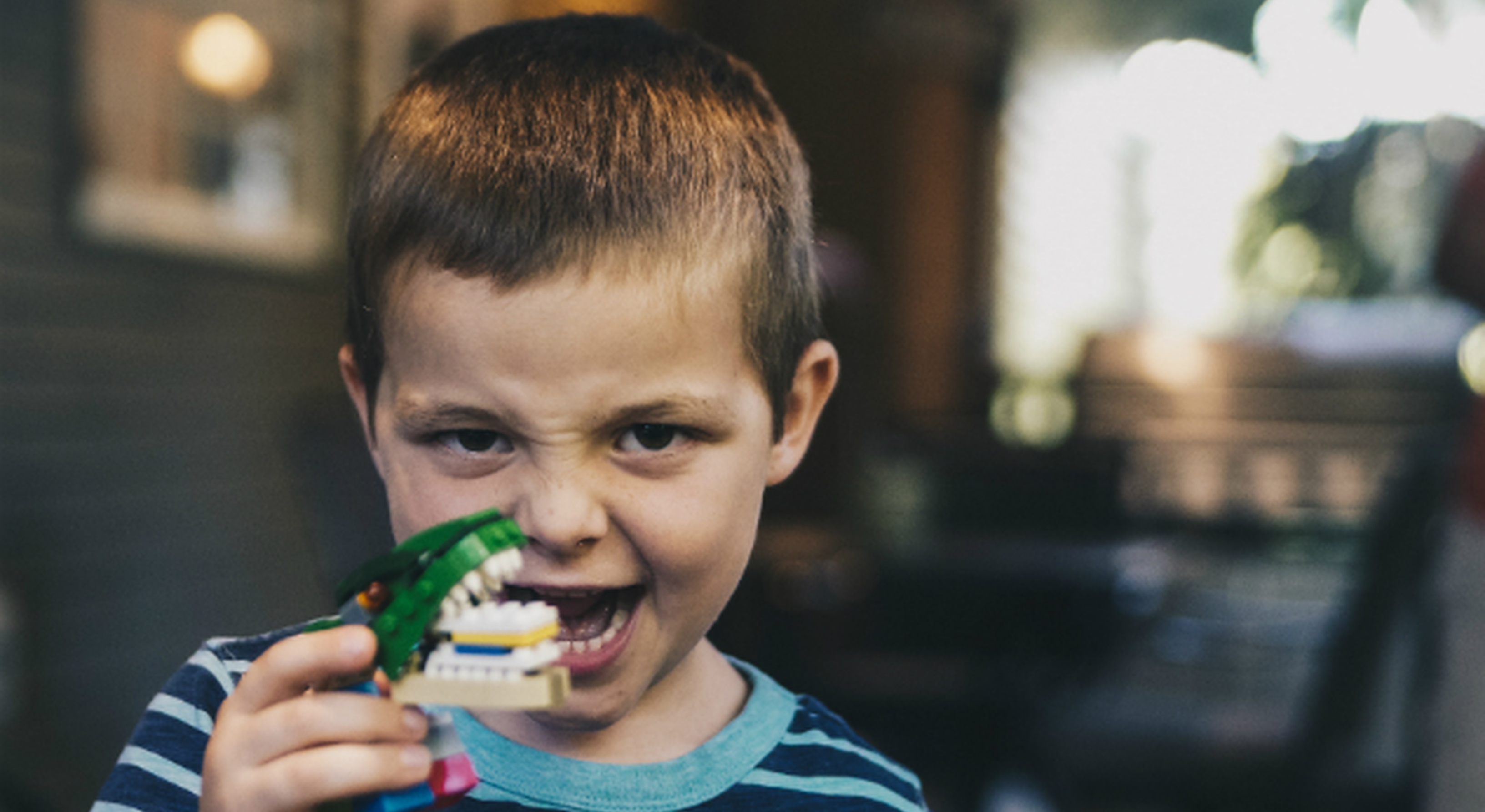 Toddler playing with dinosaur lego toy with teeth