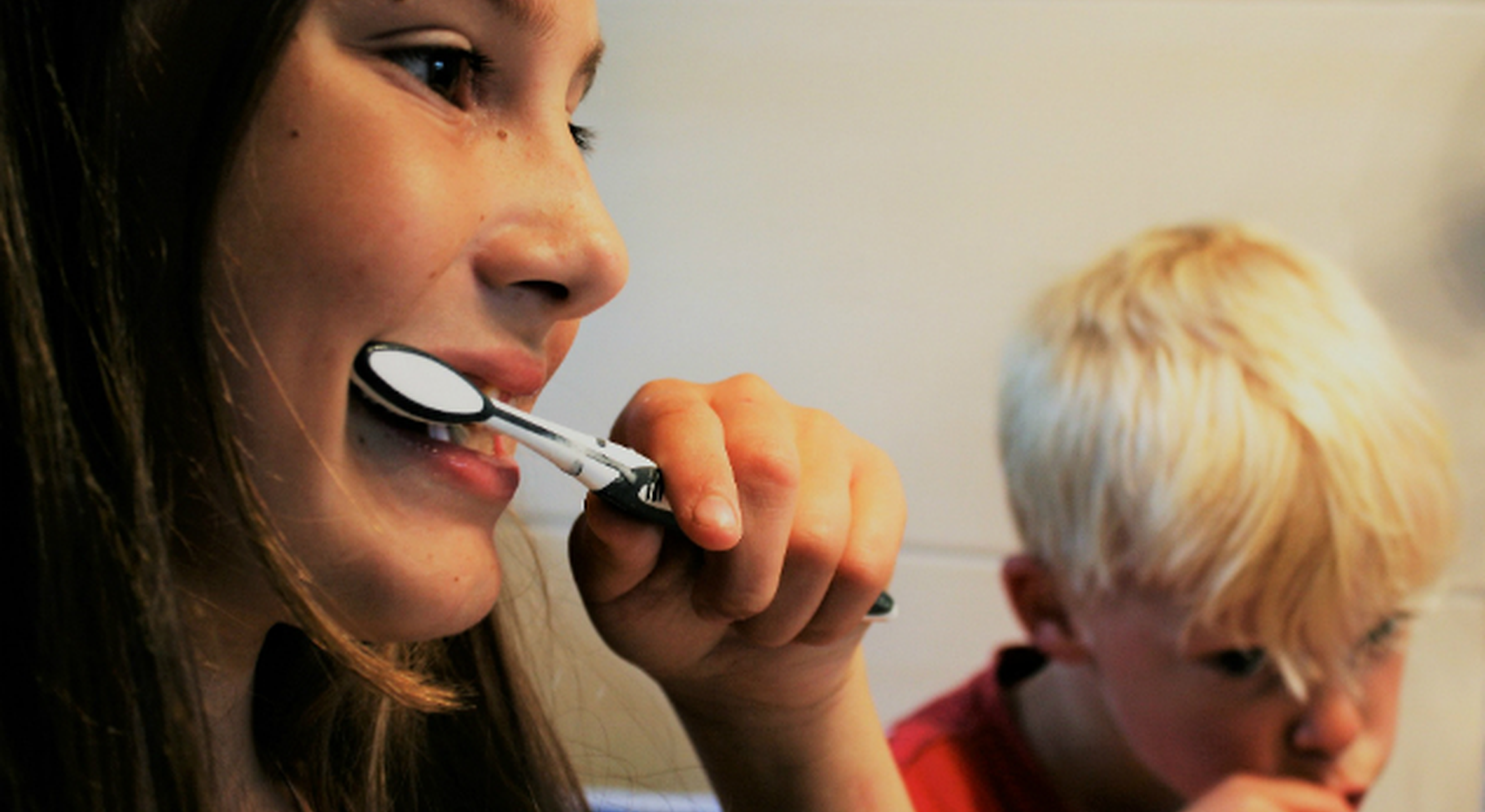 Two children brushing their teeth together