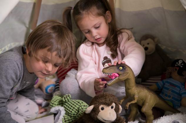 A little girls stuffs playdough in a dinosaur's mouth]