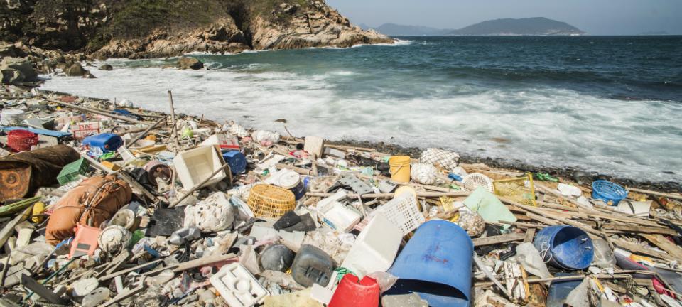 Trash covers a sandy beach]