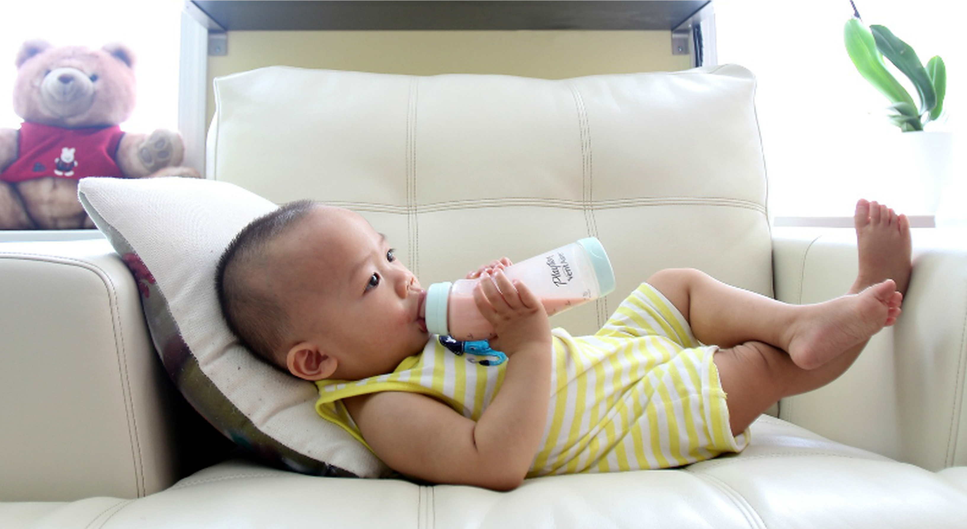 Toddler on sofa drinking pink liquid from a nursing bottle