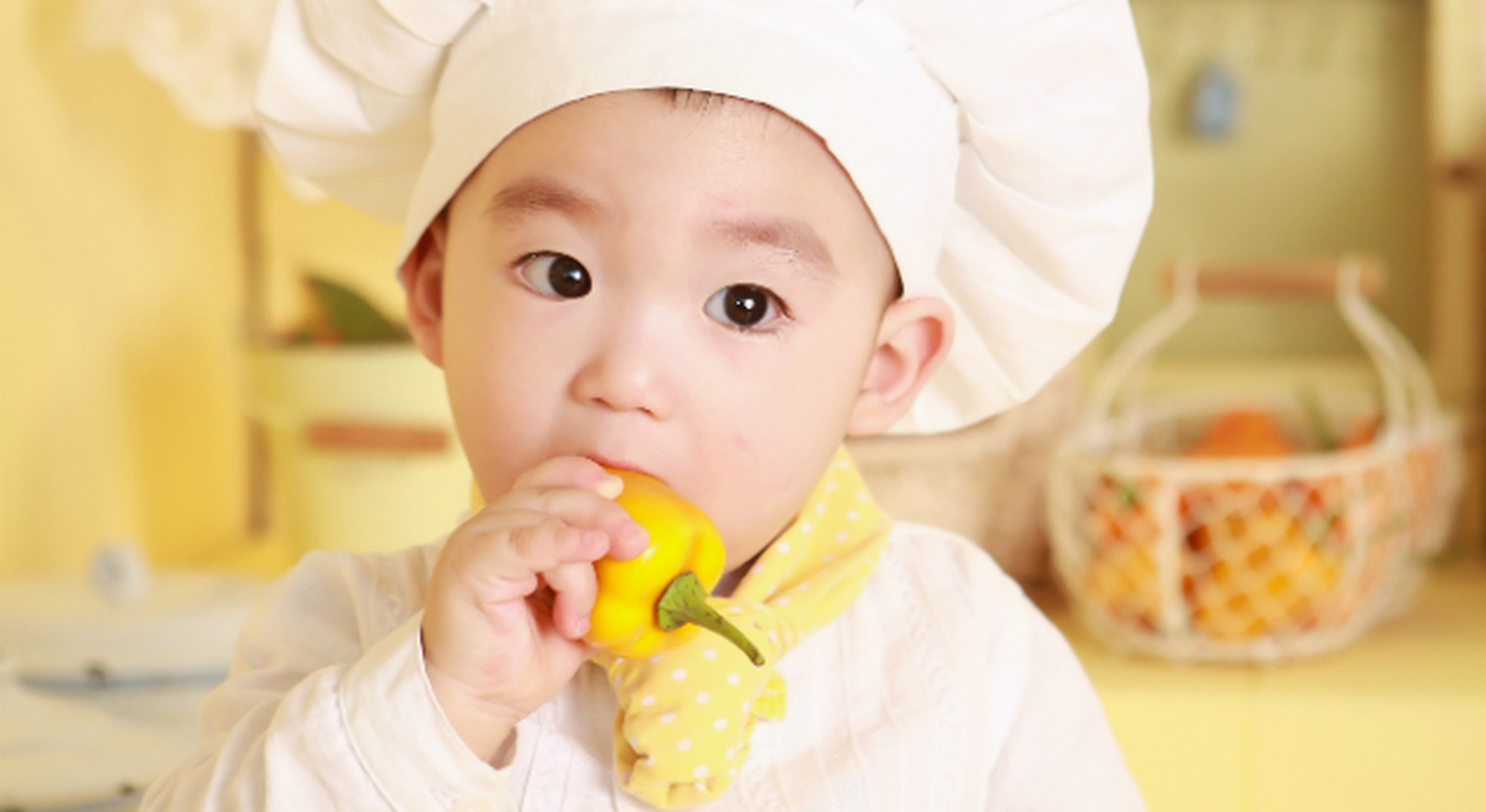 Little boy in chef hat eating yellow pepper