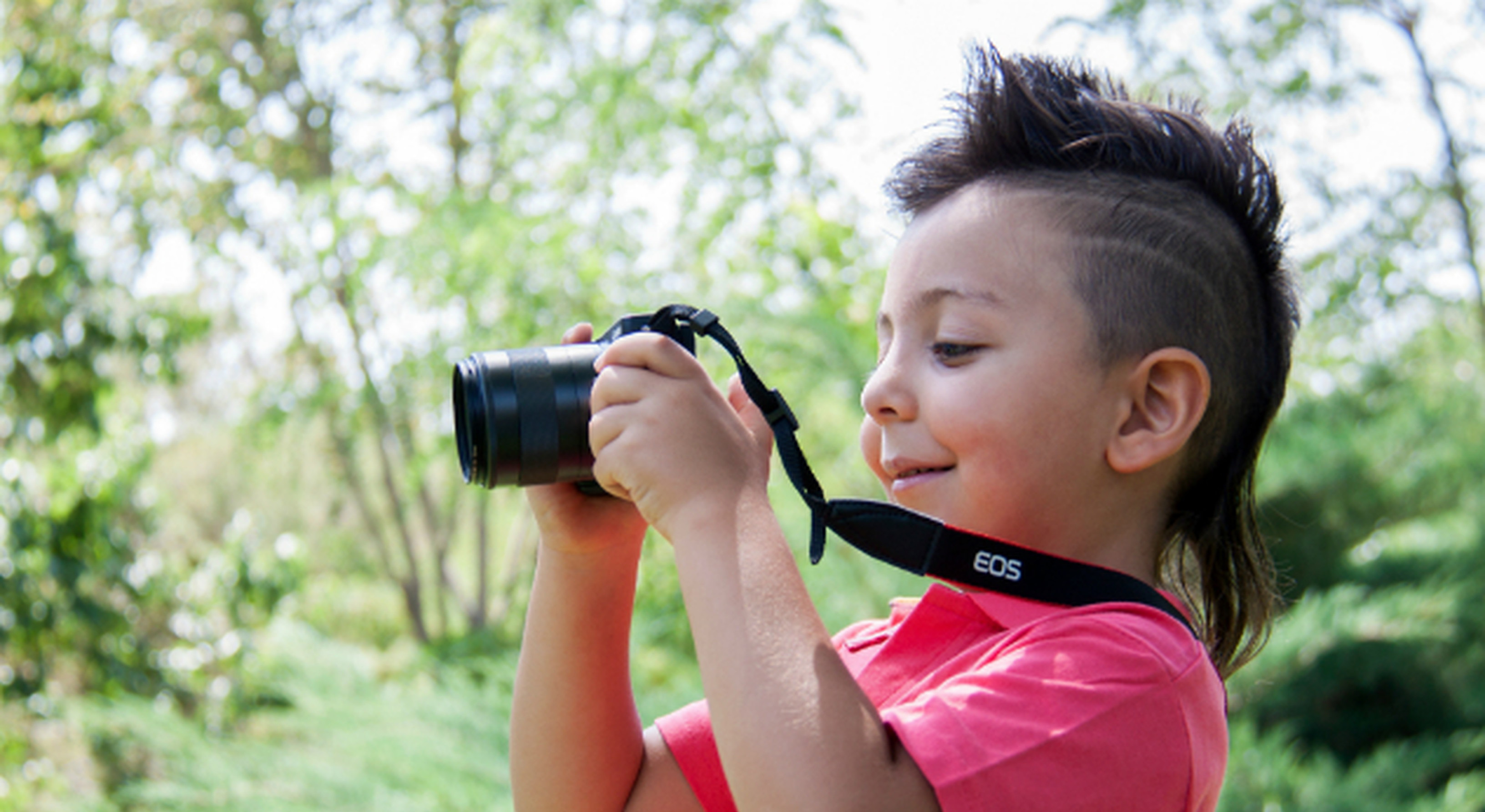 Little boy using DSLR camera outside