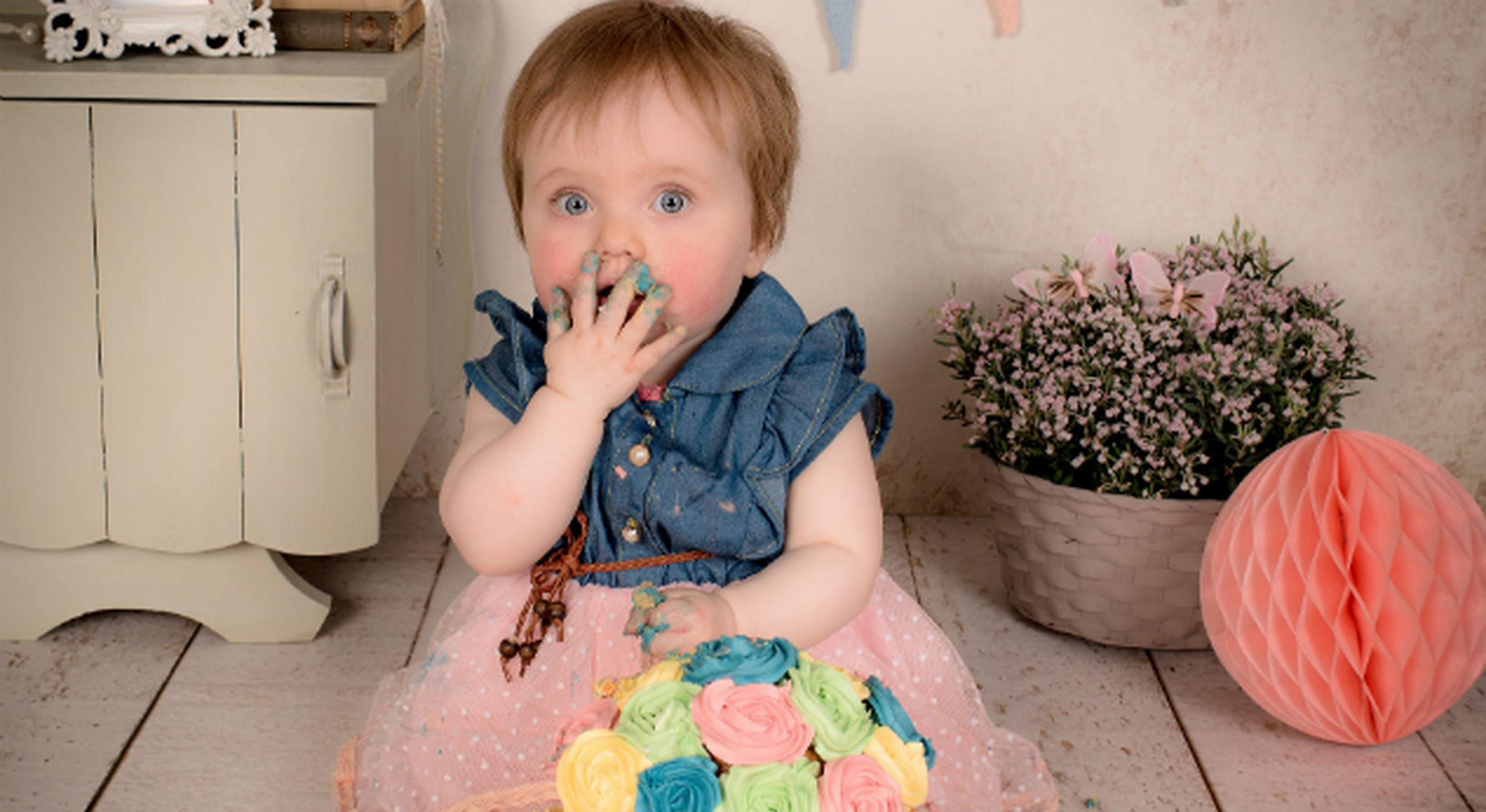 Blue eyes toddler girl eating sweets with dirty hands