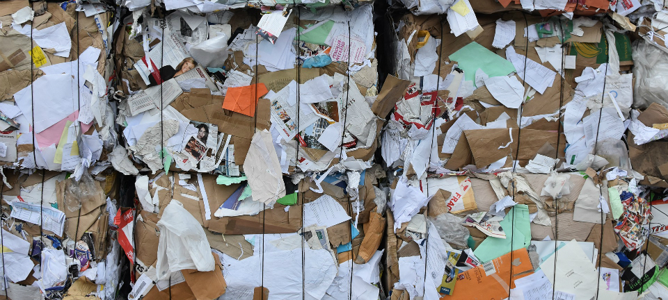 Bundles of compacted paper sit ready for recycling