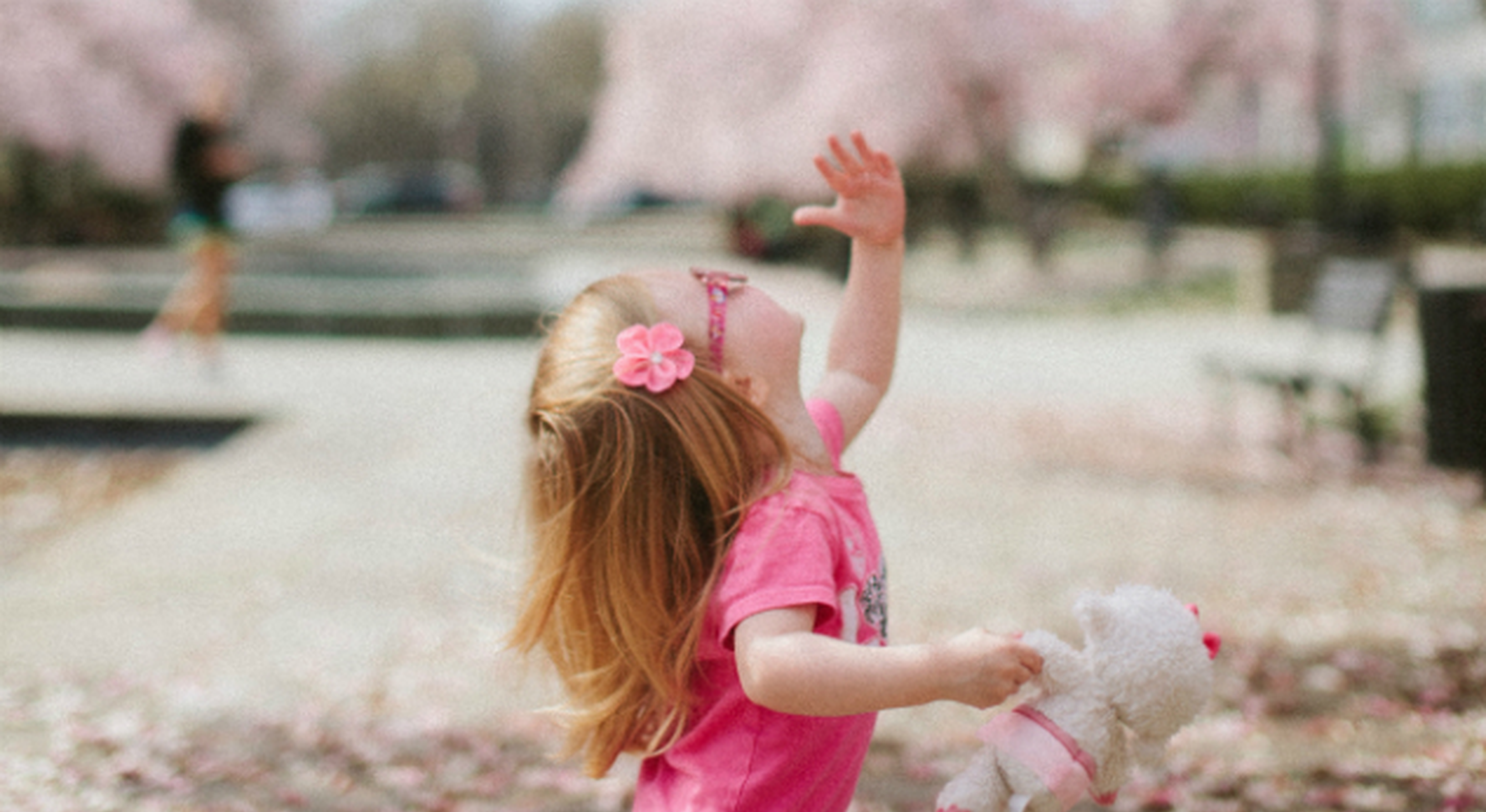 Young girl in glasses surrounded by tree blossom