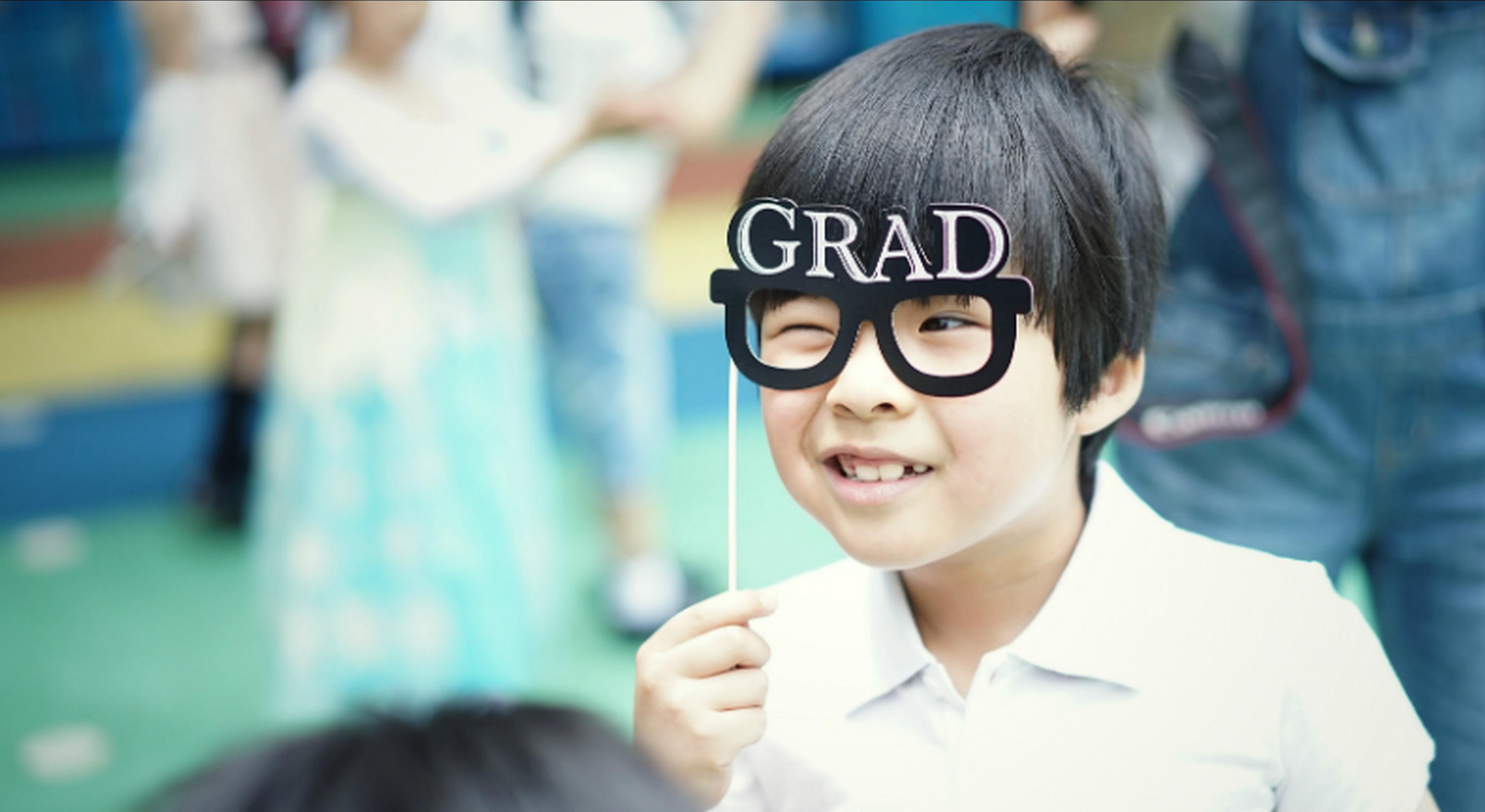 Child wearing joke graduation glasses