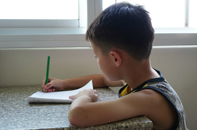 A boy sits at a table doing his homework]
