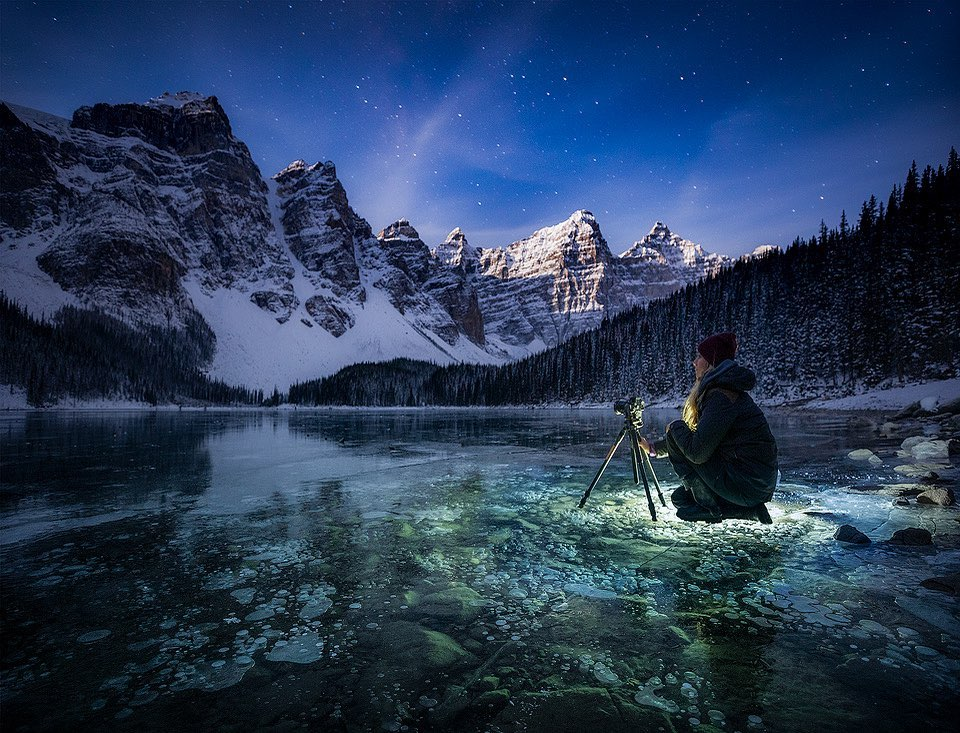 girl taking photo of snow covered mountains