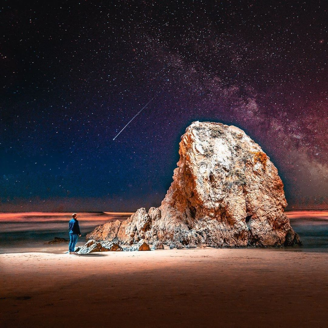 man standing in front of large rock boulder on beach