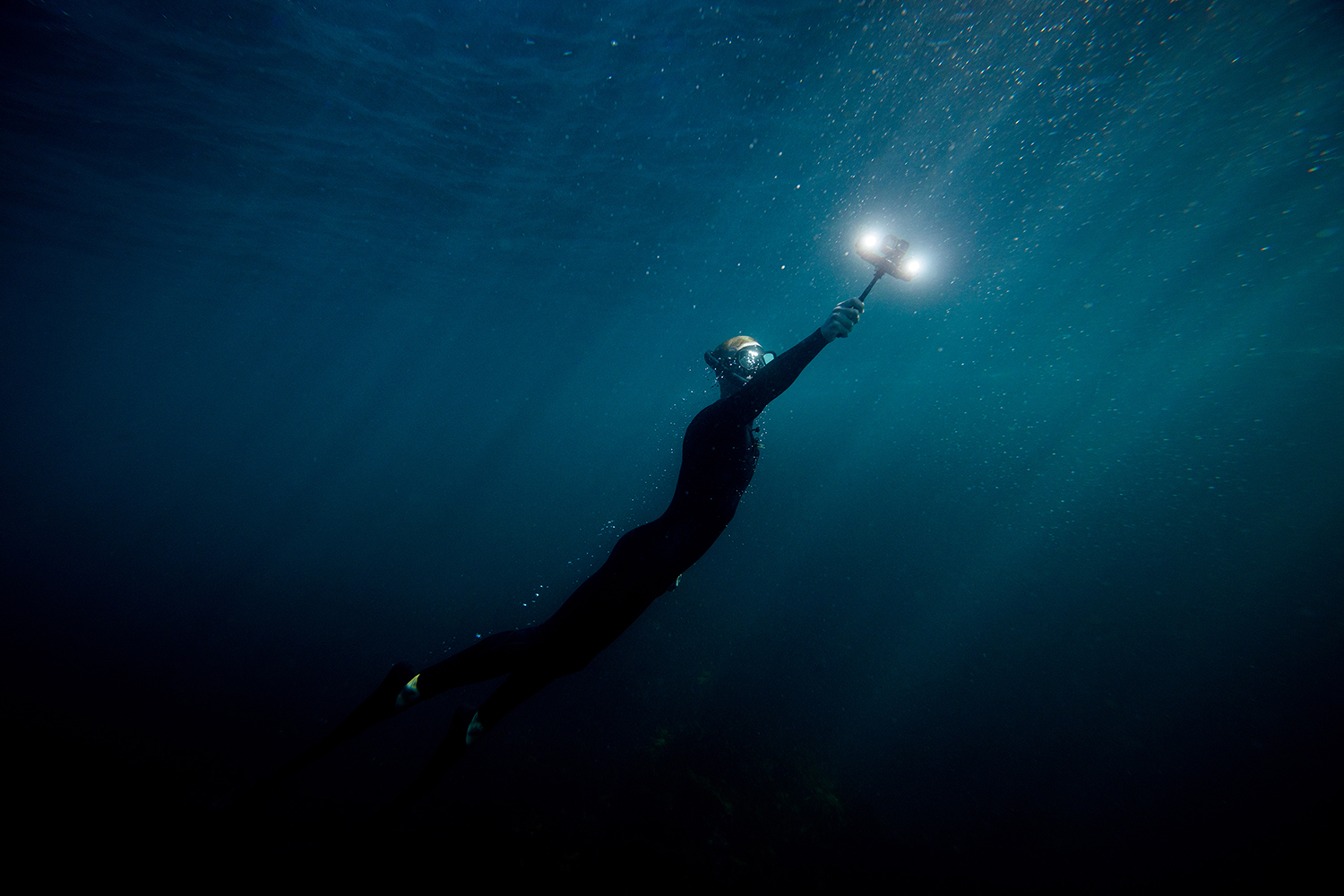man diving swimming back up to ocean surface holding lume cube 2.0 light