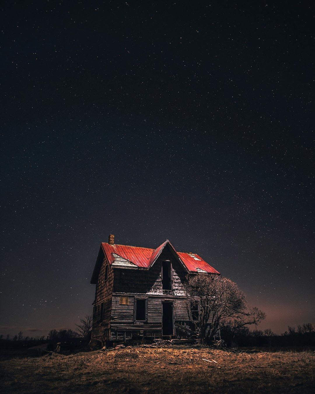 abandoned house under night sky in a field