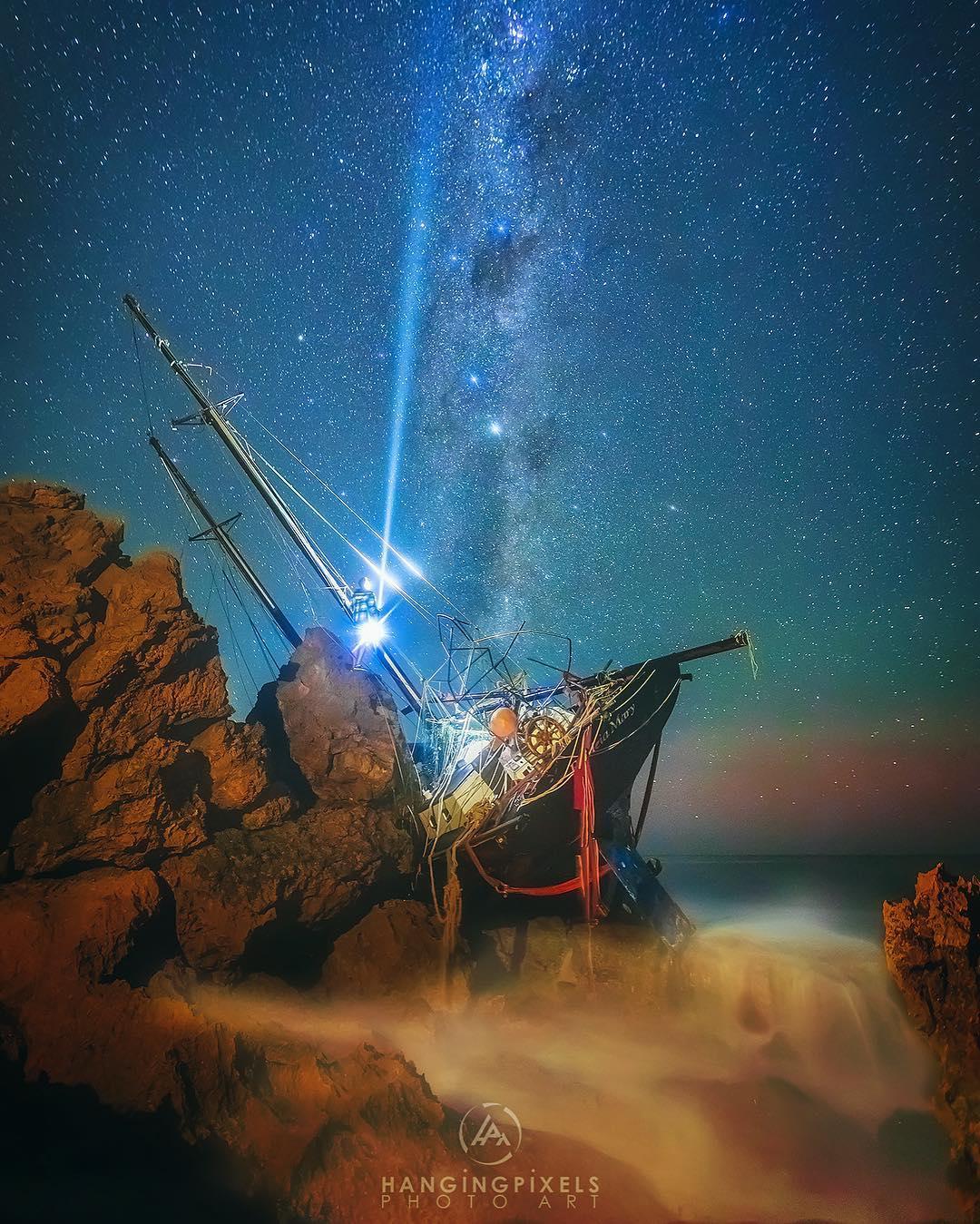 abandoned ship washed up on rocks of ocean