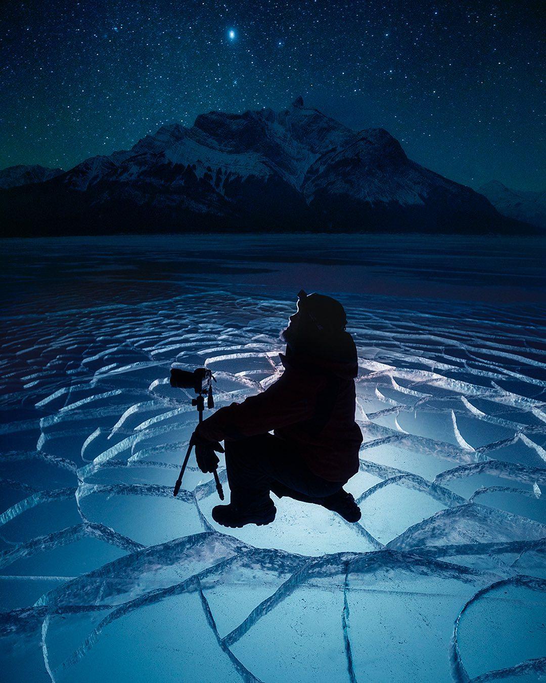 man kneeling on cracked iced over lake
