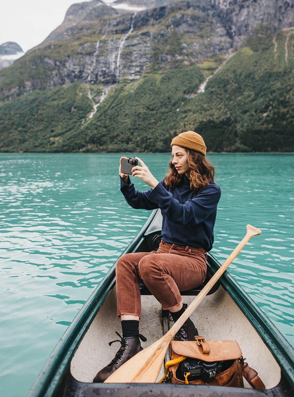 girl sitting in kayak taking photo of lake view on iphone