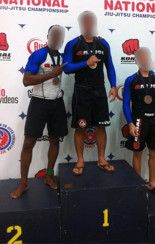 Contestants at Jiu-Jitsu championship stand on winners' podium