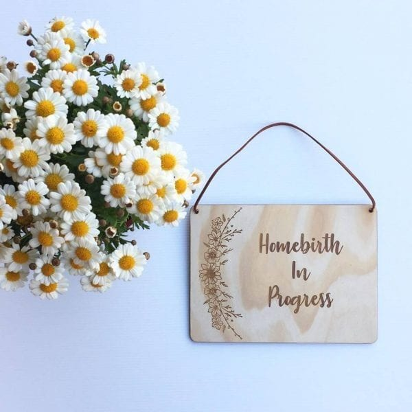 """chamomile flowers and a sign reading """"home birth in progress"""""""