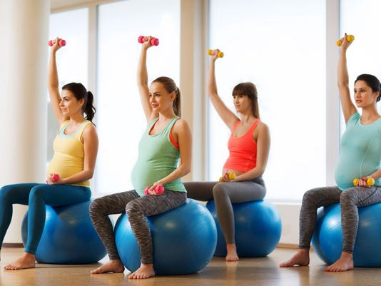 prenatal fitness class, pregnant mamas on yoga balls using light weights