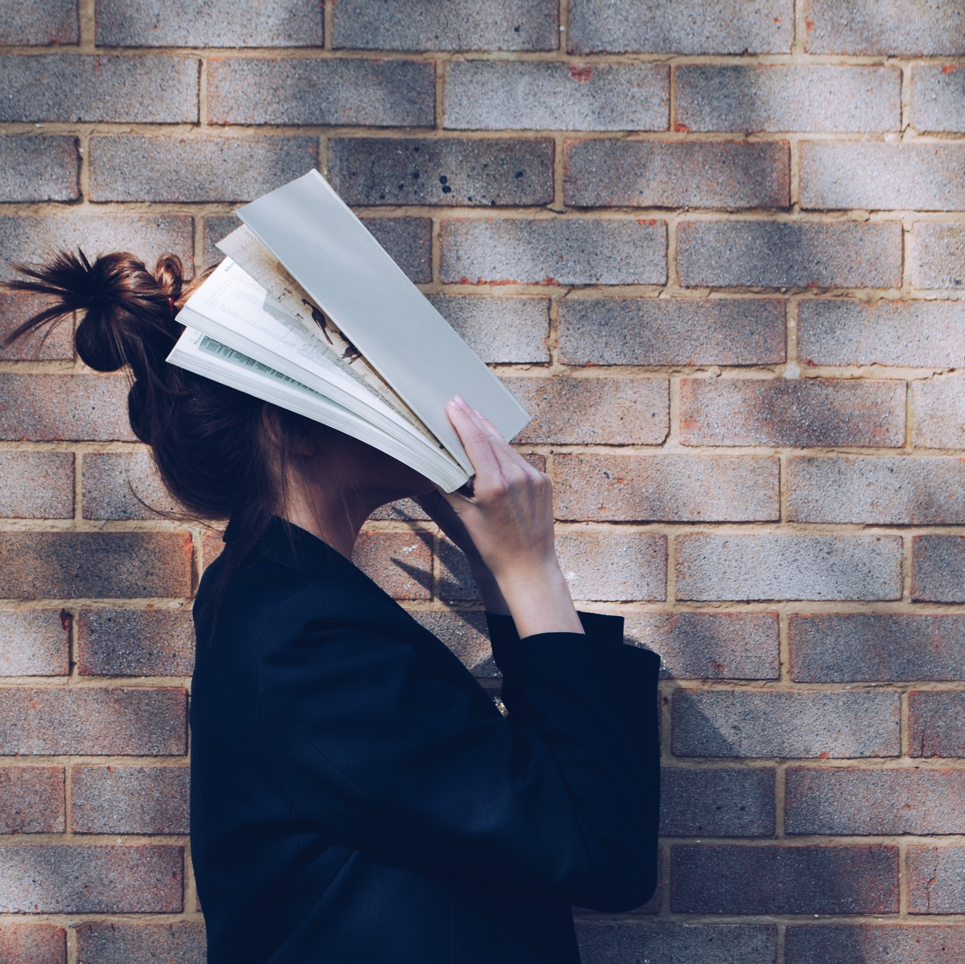 Women covering face with book