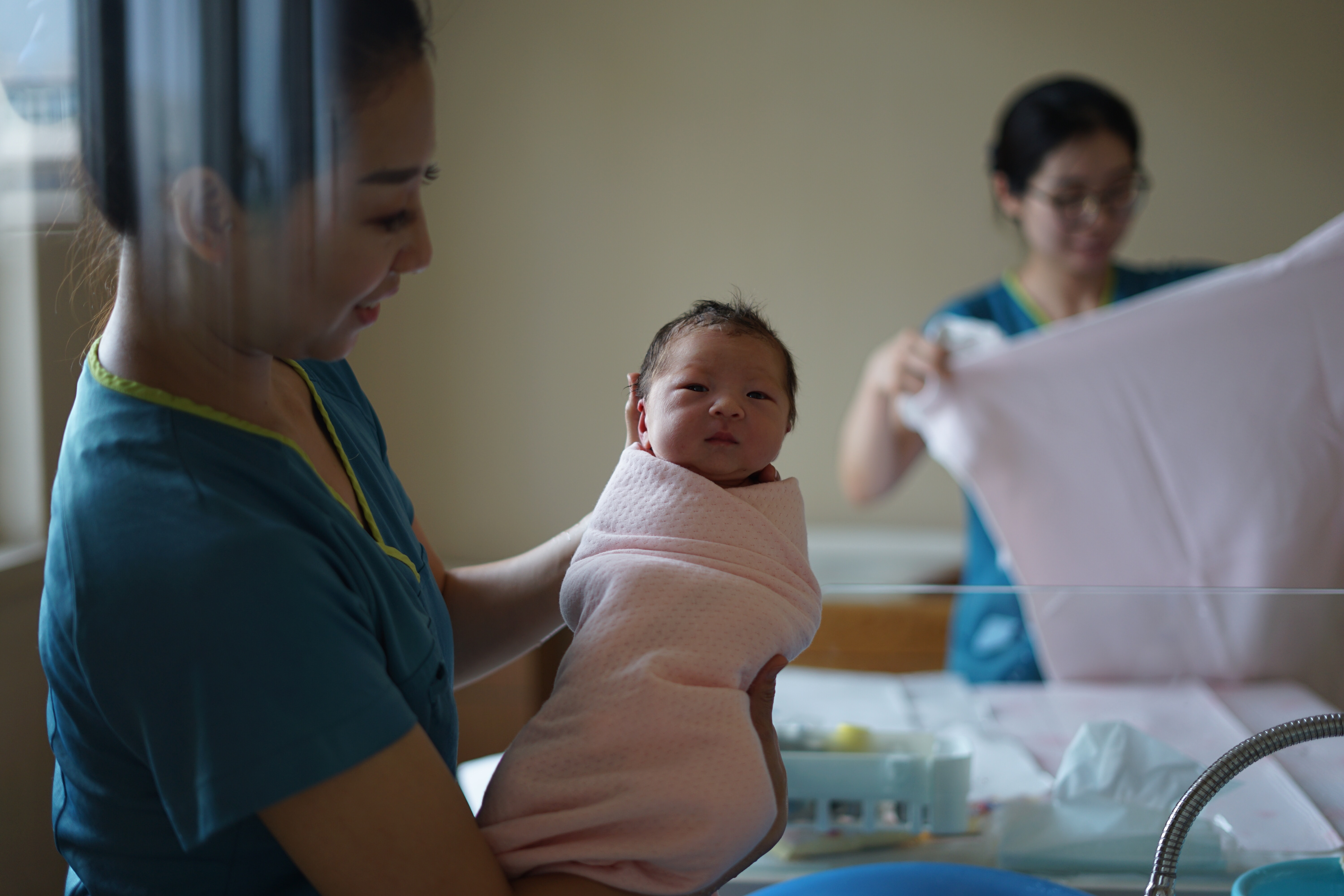Midwife holding up a swaddled newborn baby