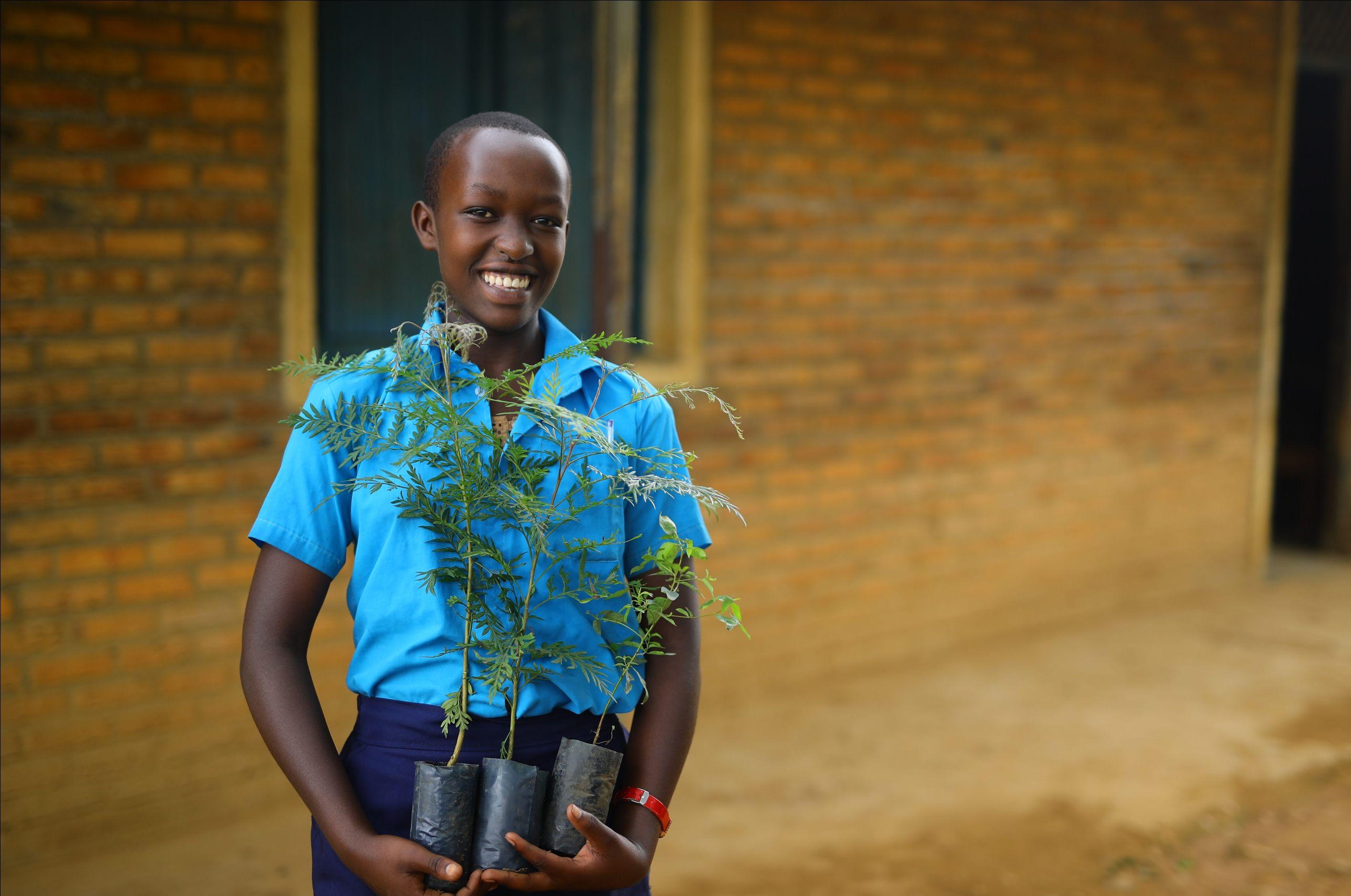 a smiling girl in Rwanda, holding tree seedlings